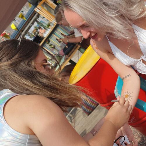 Meisje krijgt een glittertattoo op haar arm van onze glitteraar, tijdens indiburn Festival op Beachclub Indigo Scheveningen Den Haag
